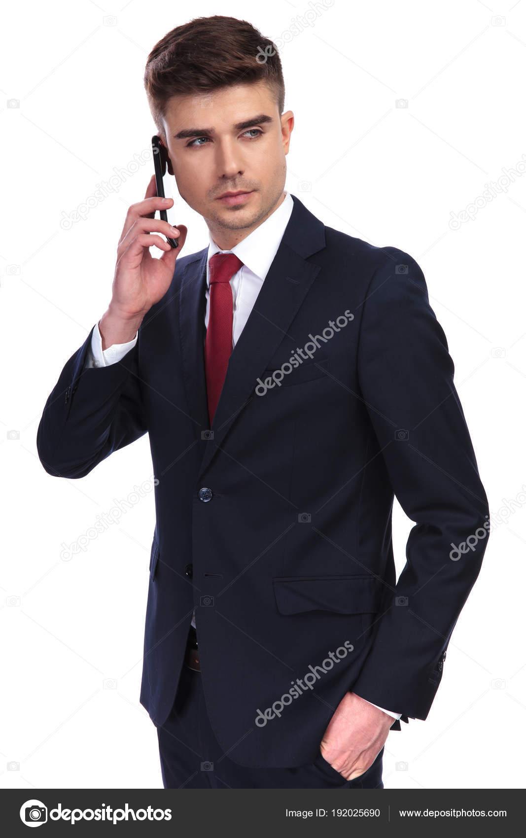 7bc5af9605fd9 Portrait d'homme d'affaires décontractée, parler au téléphone tout en  regardant de côté, debout sur fond blanc. Il porte un costume marine et une  cravate ...