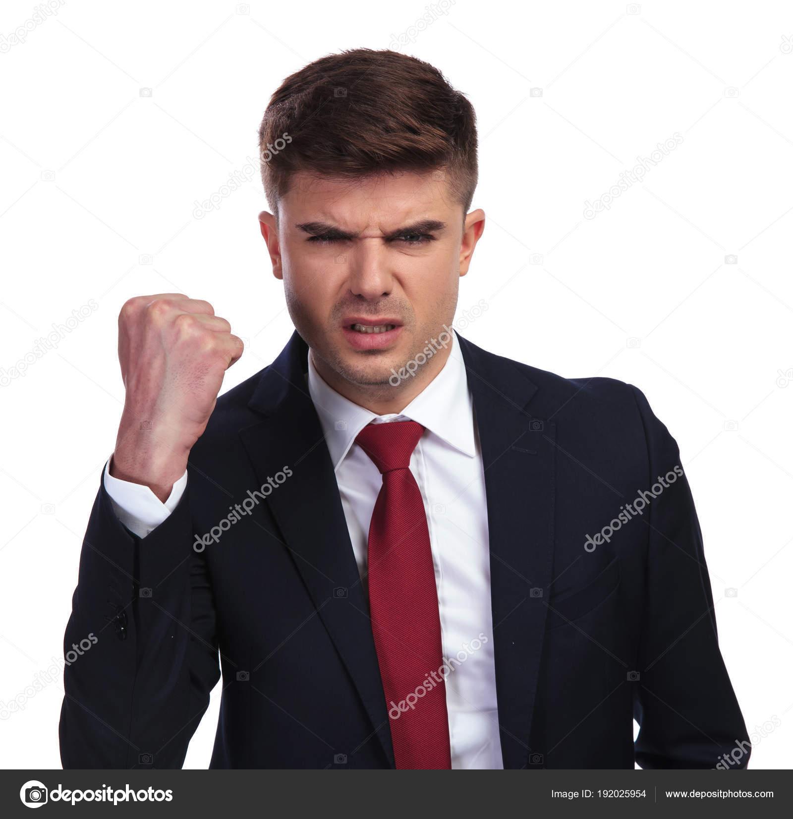 34f390ef36a92 Portrait d'homme d'affaires en colère, agitant son poing sur fond blanc. Il  porte un costume de couleur marine et une cravate rouge. — Image de feedough