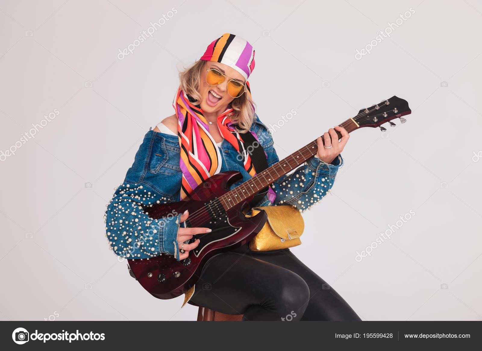 Belle femme avec foulard coloré jouant une chanson rock à la guitare en  position assise sur une chaise en bois sur fond gris clair — Image de  feedough e634428f935