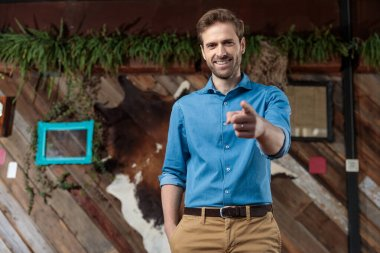 Happy casual man pointing forward and smiling