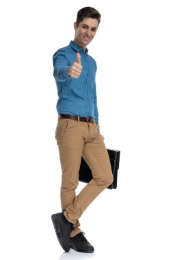 smart casual man making thumbs up sign and holding suitcase