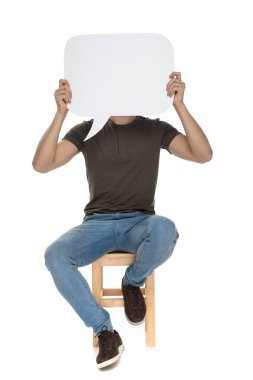 Charming casual man covering his face with a blank speech bubble, sitting on a chair on white studio background