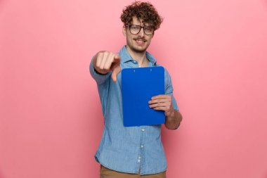 young casual guy in denim shirt holding clipboard and pointing finger, standing on pink background