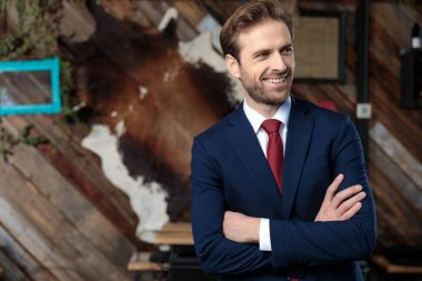 confident young businessman smiling and crossing arms, looking to side in a coffeeshop