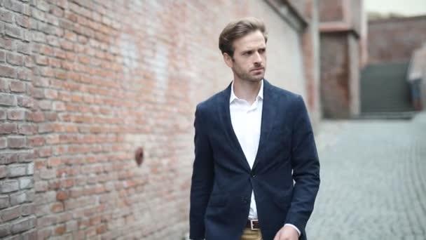 blonďatý podnikatel kráčí s jednou rukou v kapse a rozhlíží se, venkovní