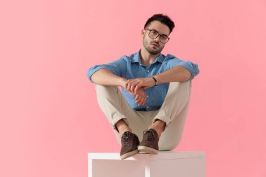young businessman wearing glasses sitting with legs resting on cube and looking at camera serious on pink studio background