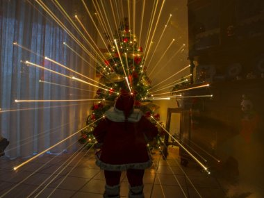 christmas night in house with doll santa claus and effect warm lights fireworks of christmas tree