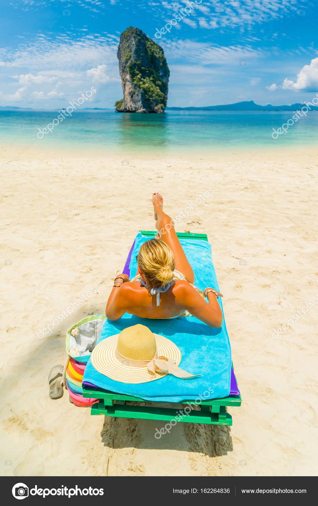 frau sitzt auf einem bett am strand stockfoto netfalls 162264836. Black Bedroom Furniture Sets. Home Design Ideas