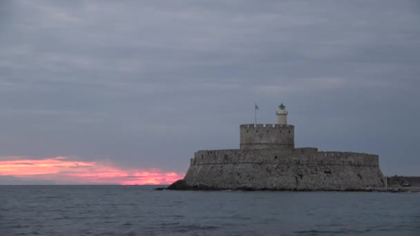 Agios Nikolaos fortress on the Mandraki harbour of Rhodes Greece at sunset
