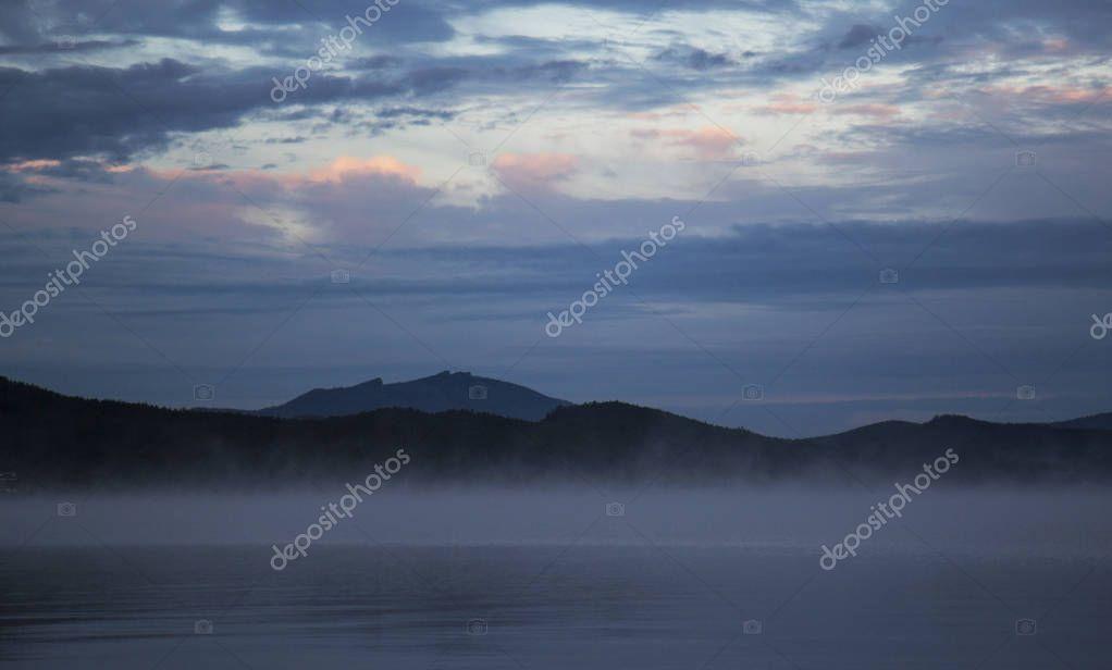 Borovoe lake during sunrise, sleeping knight mountain and smoke on the water, Burabay National park in Northern Kazakhstan.