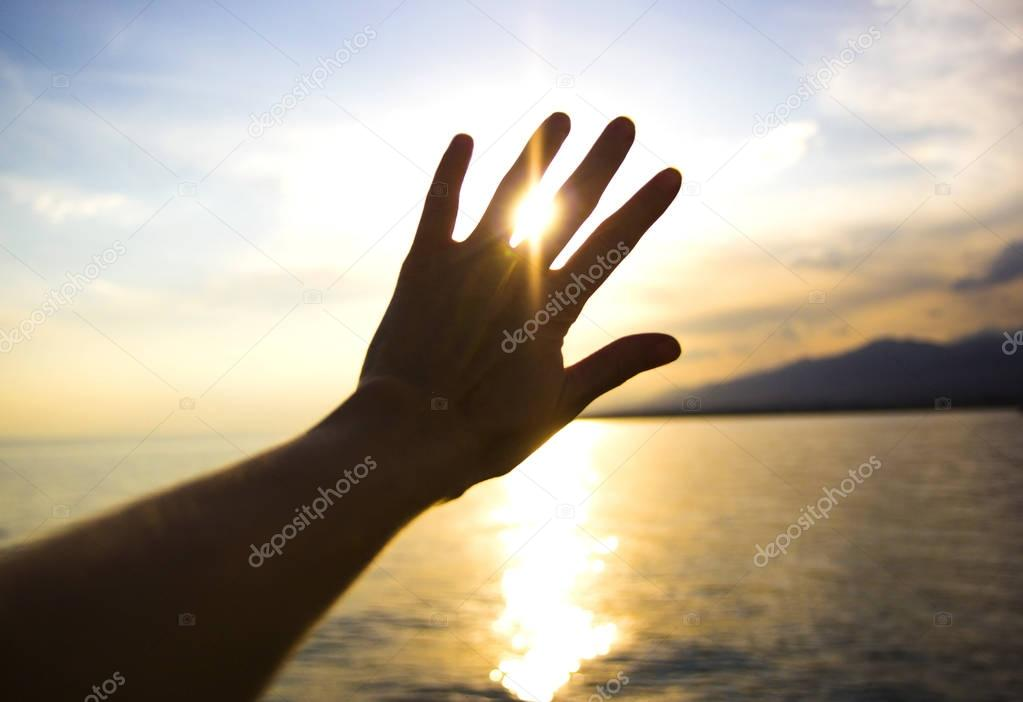 sun shining through the fingers of the hand on the sea background