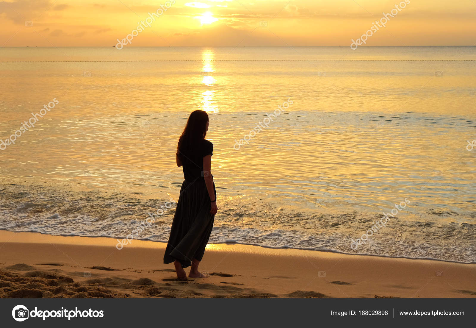 Lonely girl walking on the beach at the sunset — Stock Photo