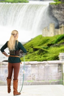 Female elf looking at castle holding bow with waterfall in background stock vector