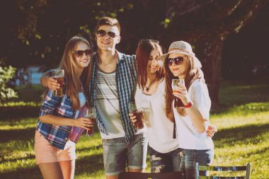 Cheerful friends drinking beer on picnic in park.