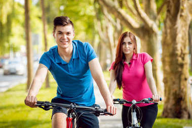 Young caucasian couple cycling on green bicycle lane in sunny day