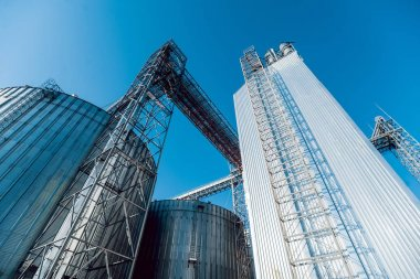 Modern silos for storing grain harvest. Agriculture. Low angle.
