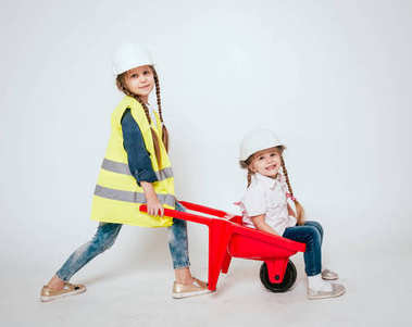 Two little cheerful girls with braids playing in repair or construction on white