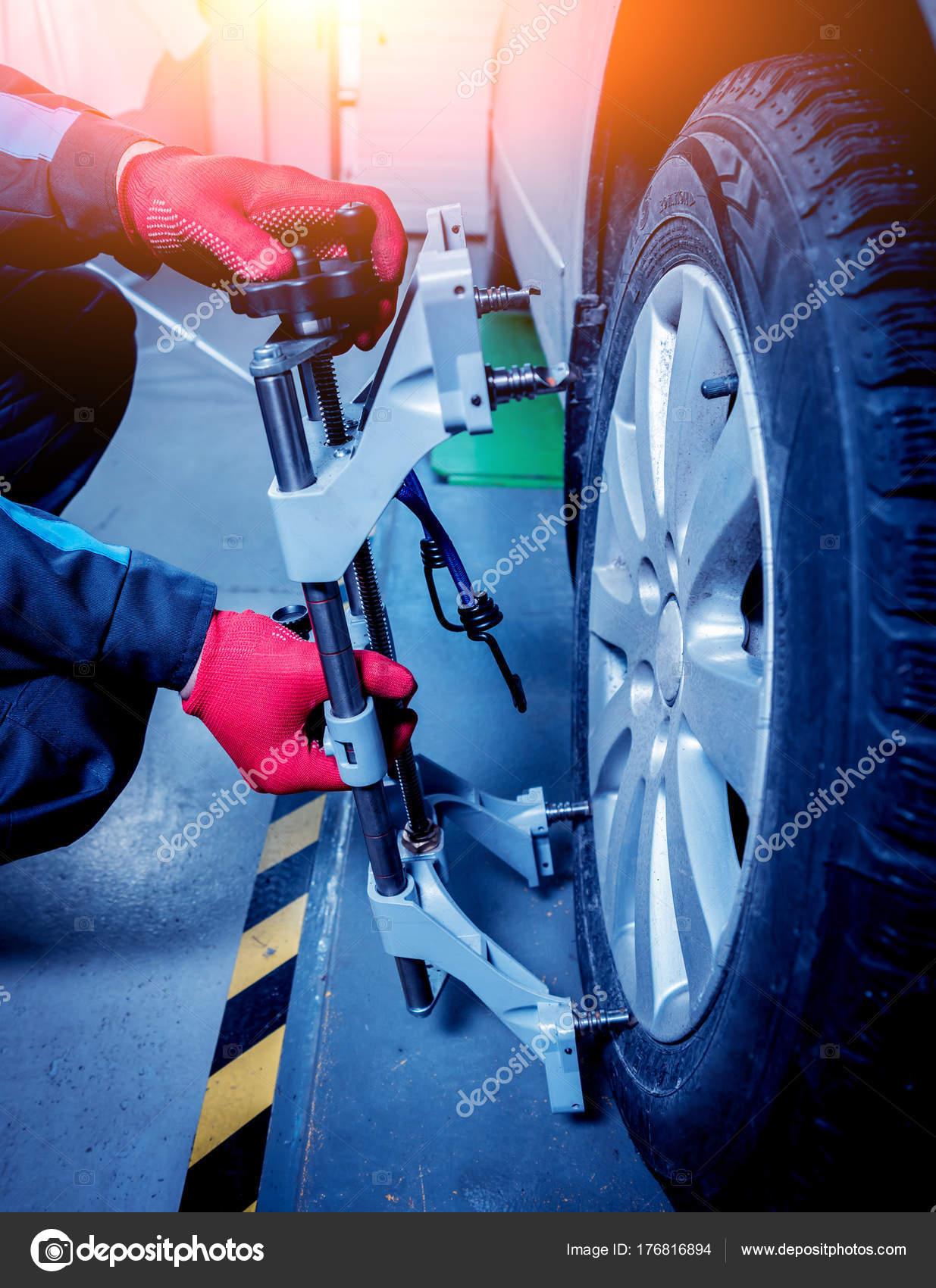 car mechanic installing sensor suspension adjustment wheel alignment