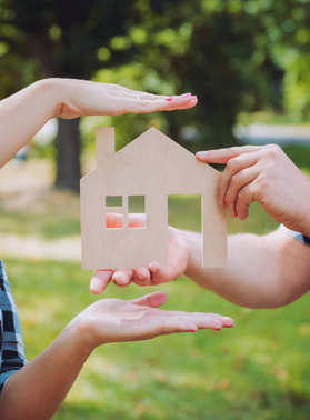 Young woman holding model of house at her hands. Outdoors. Summertime. Real estate and property concept