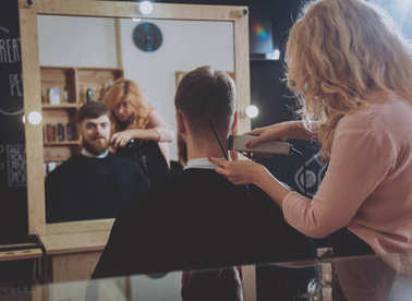 Hairdresser makes hairstyle for a young man.