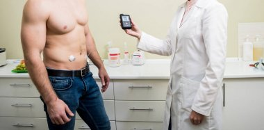 The doctor connects an insulin pump to a patient with diabetes. A concept of diabetes.