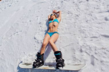 Attractive young woman dressed in swimsuit with snowboard laying on snow