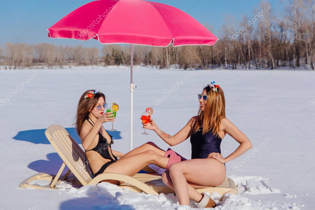Two young women in bikini posing with cocktails on a sun bed.