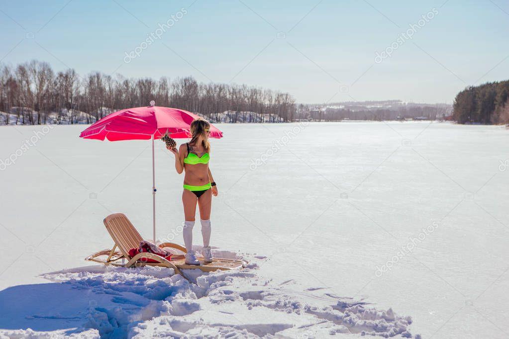 Young woman in bikini posing with pineapple near sun bed.