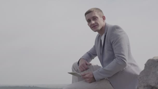 atraktivní mladý obchodník sedí na skále a ukazuje palcem nahoru