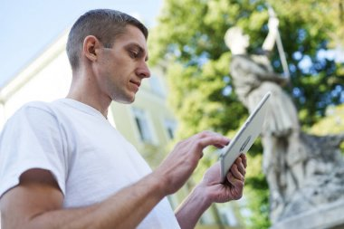 young handsome man standing in the street looking for something on his tablet