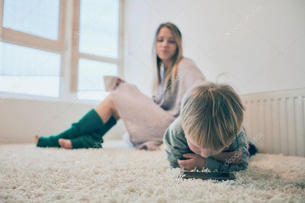 Blonde young mother sitting on the sofa with a cap in green socks and baby lying next played