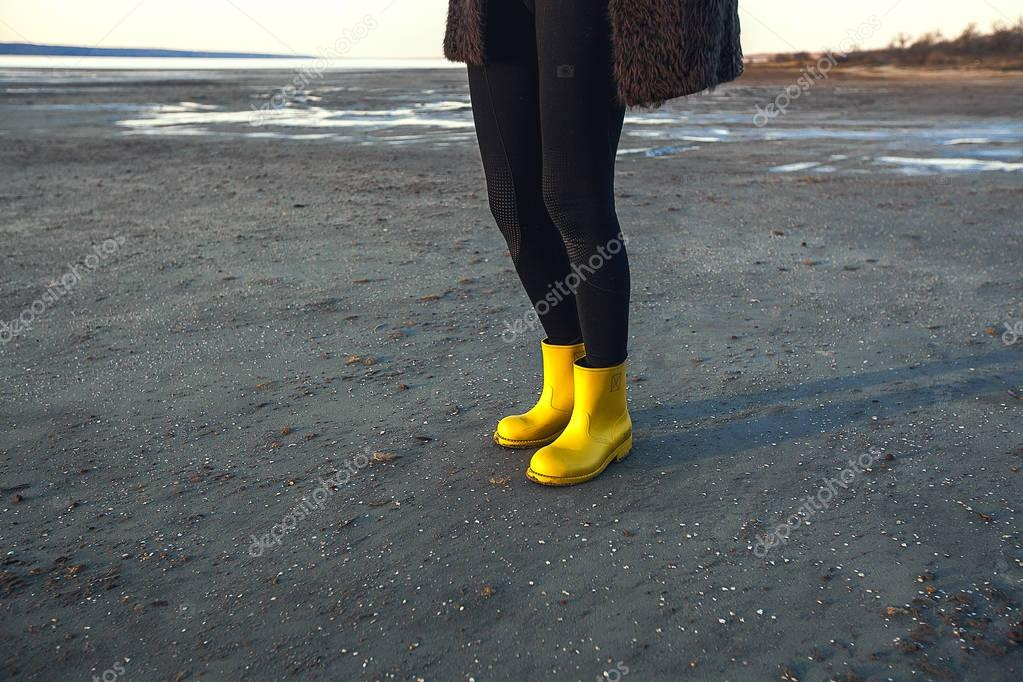 Girl in boots walks on the lake