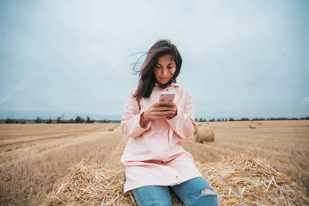 girl on haystack using mobile