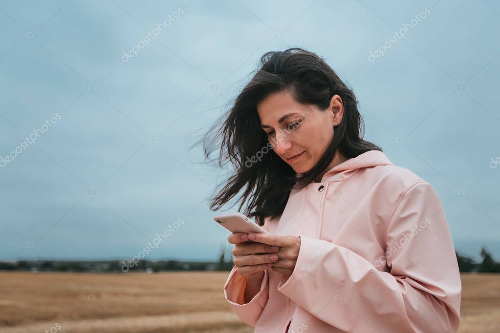girl using mobile in autumn field