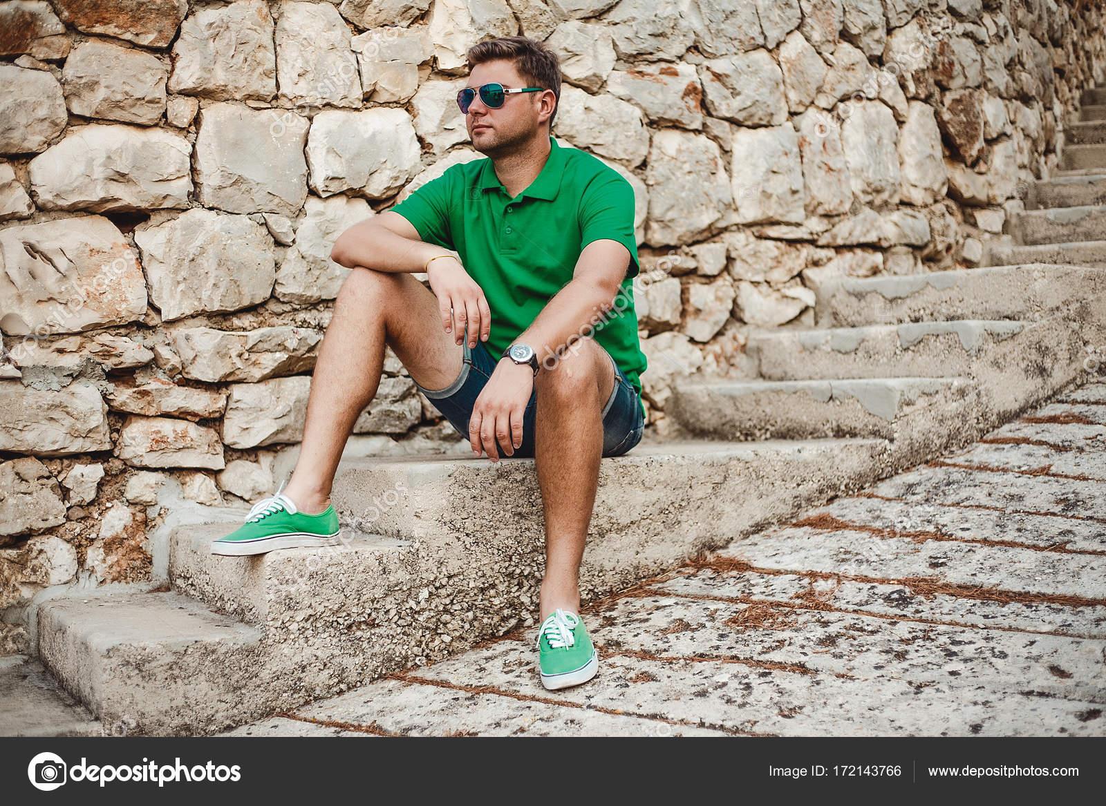 Jovem homem forte em óculos de sol sentado na escada de pedra — Foto de  evgeniyregulyan gmail.com ede9f2f1c0