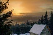 Gyönyörű naplemente a havas téli hegyek, a fából készült ház