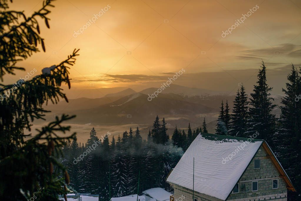 Beautiful sunset in snowy winter mountains with wooden house