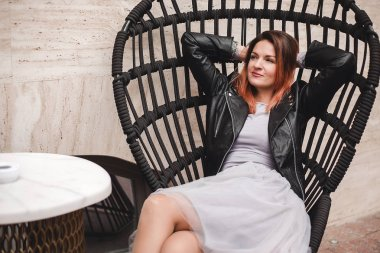 young beautiful woman posing sitting in chair in city street