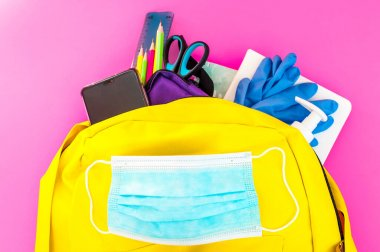 Yellow backpack full of school must-have tools also with face mask, hydro alcoholic gel and latex gloves to protect from covid-19 on the pink background
