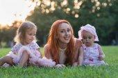 Matka s dvěma dcerami sedí v parku