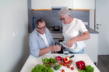 Senior couple drinking water in the kitchen. Elderly man and woman cooking together. Domestic kitchen interior on background. Healthy lifestyle concept