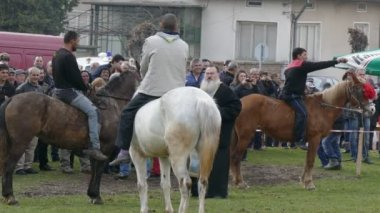 The priest sanctifies the horses and the contestants.
