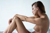 junges schönes Mädchen posiert nackt im Studio auf dem Bett sitzend