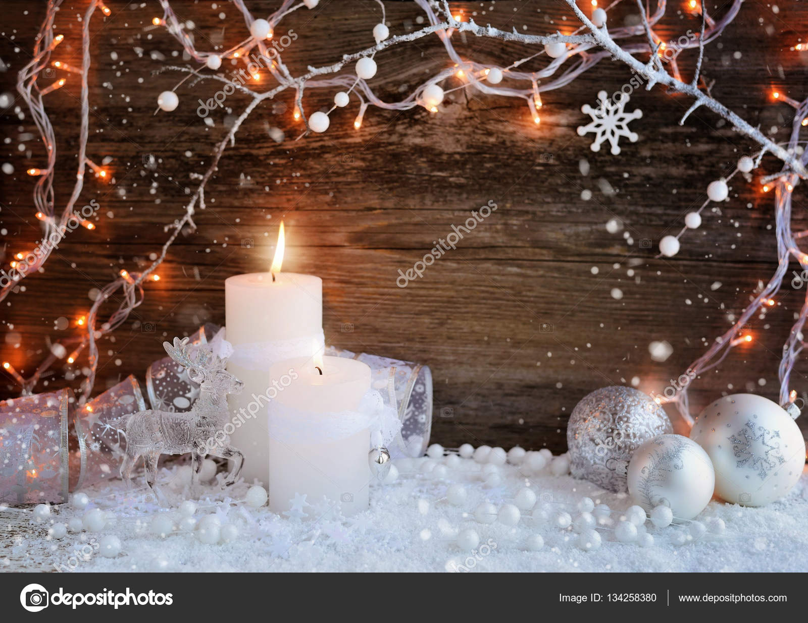 Two Burning Candles With A Deer Christmas Decorative Balls On Snow And Lights Decorations Wooden Background
