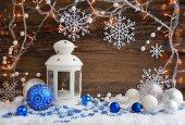 Vánoční složení s lucernou a vánoční osvětlení na dřevěné pozadí