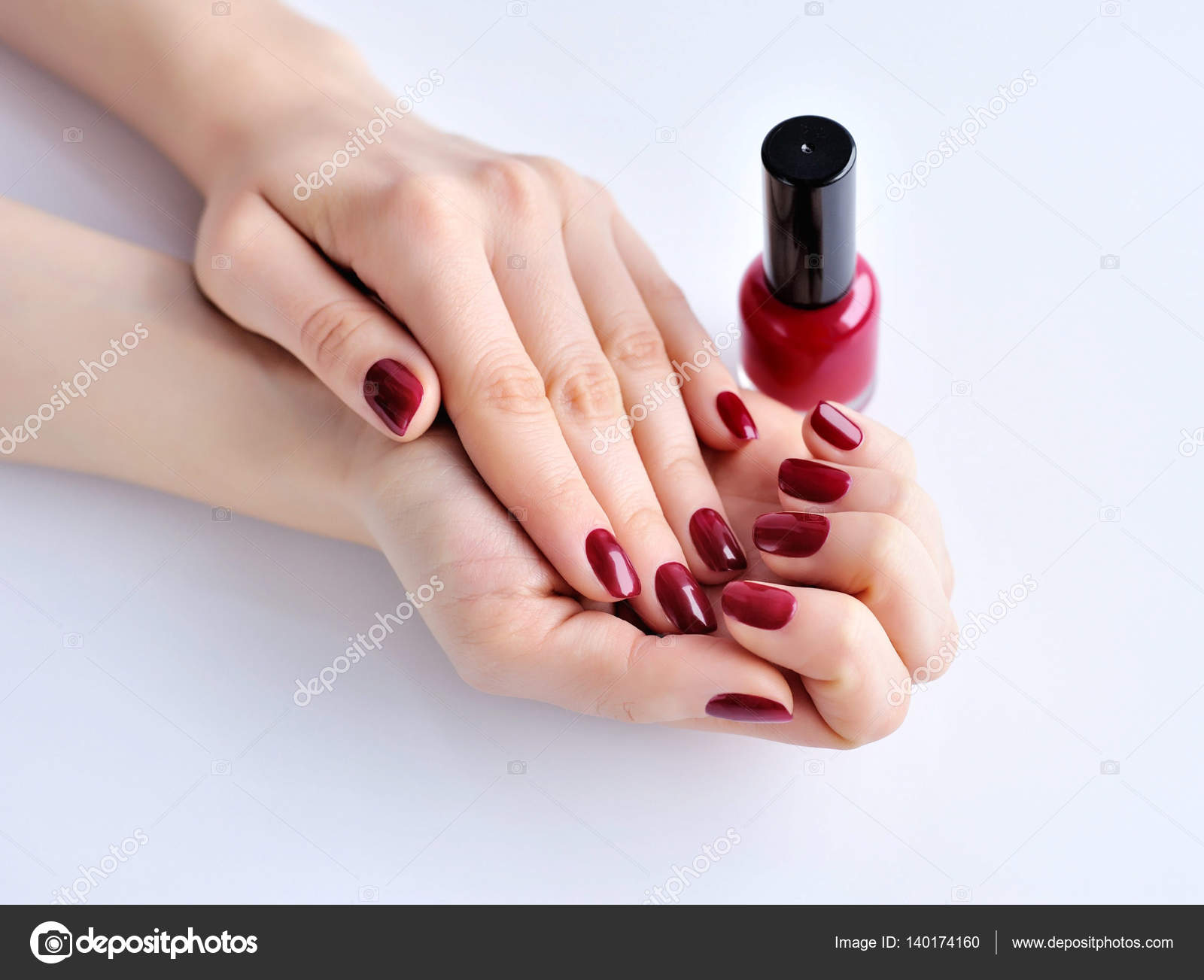 Hands of a woman with dark red manicure and nail polish bottle ...