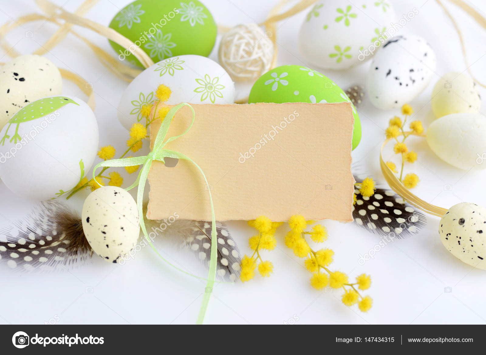 Easter eggs and mimosa flowers on white background with blank card easter eggs and mimosa flowers on white background with blank card to greet stock photo m4hsunfo