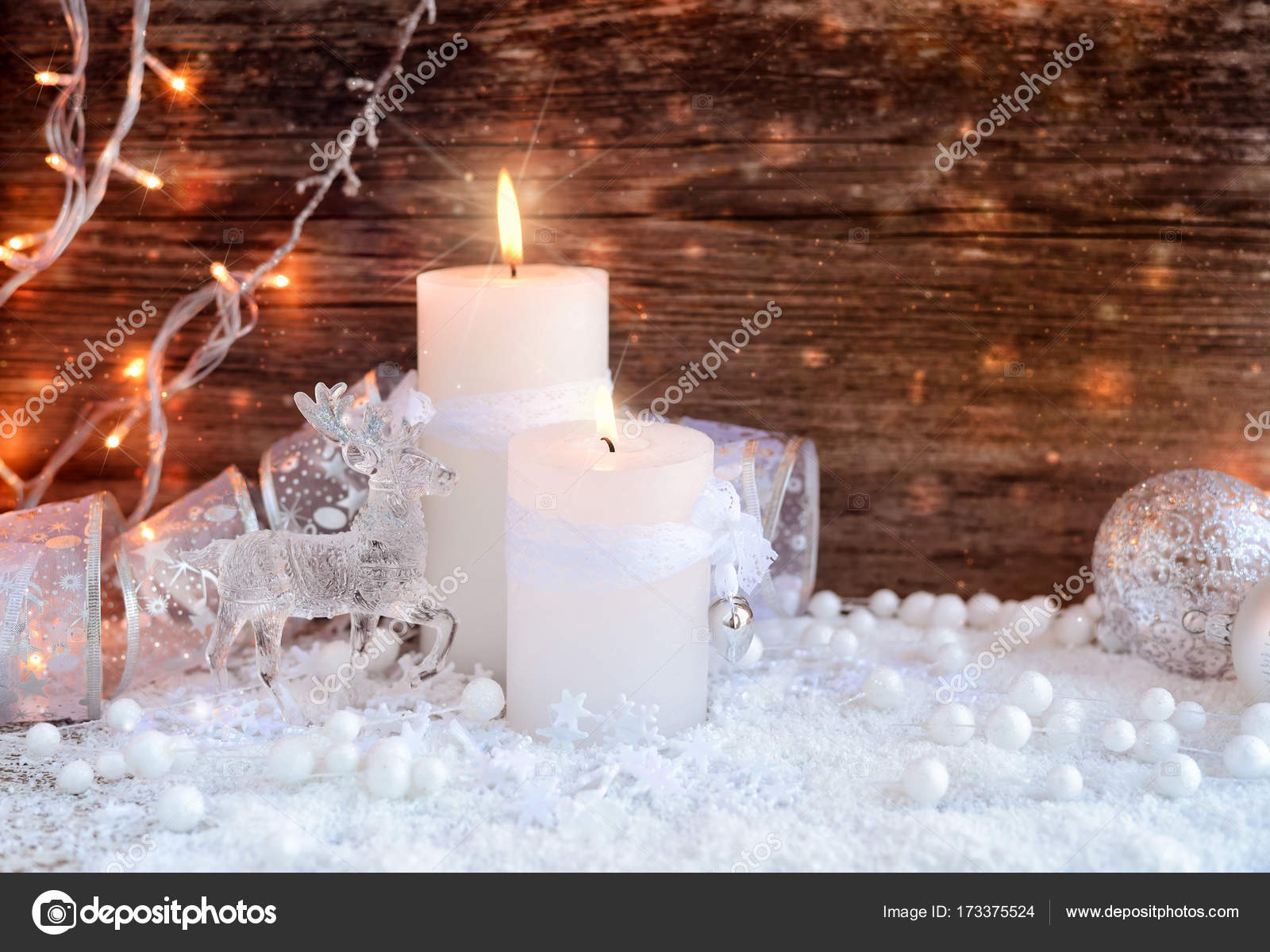 Weihnachtsbeleuchtung Schneefall.Two Burning Candles With A Deer With Christmas Decorative Balls On