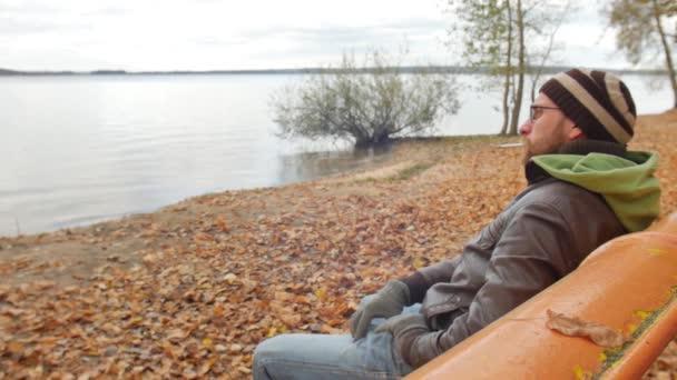 Őszén egy padon, cigarettázott a szakállas férfi válaszol egy bejövő hívás a mobiltelefon