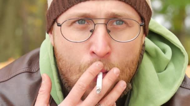 A szakállas férfi pulóver és bőr kabát, ősszel egy padon, cigarettázott exhaling füst a szobába